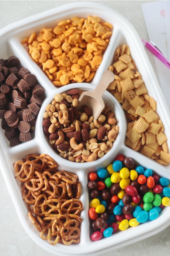 divided tray with pretzels, nuts, candy and crackers