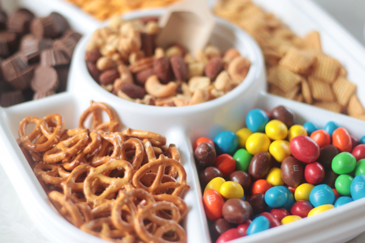 divided tray with pretzels, nuts and M&M candies