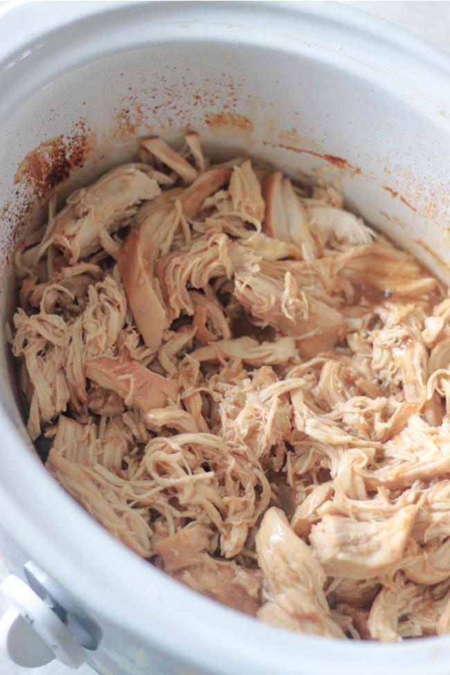 slow cooker filled with shredded chicken teriyaki