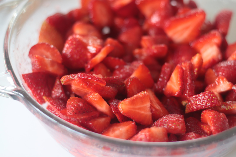 bowl of sliced strawberries and sugar