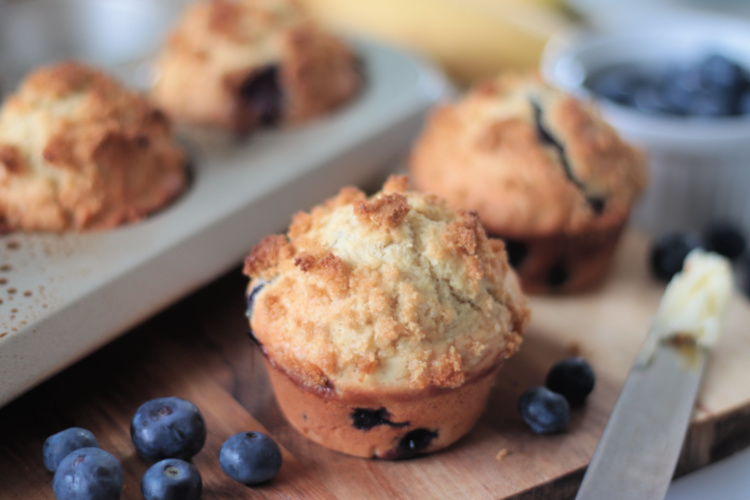 blueberry banana muffin next to pan of muffins