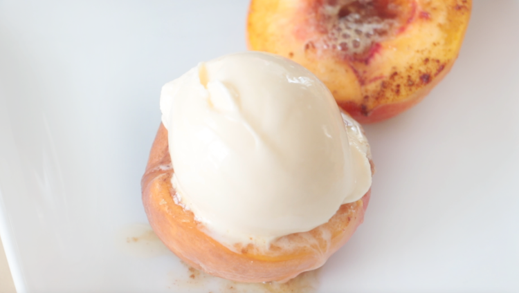 baked peaches and cream on a white plate