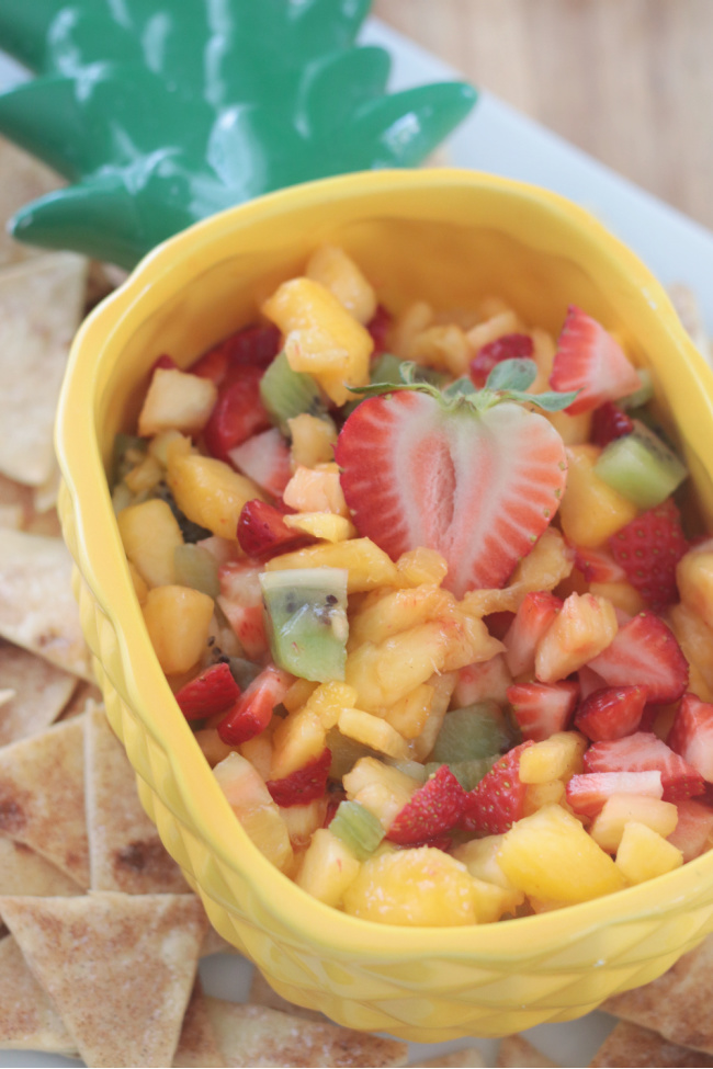 pineapple shaped bowl with chopped fruit and cinnamon chips on platter