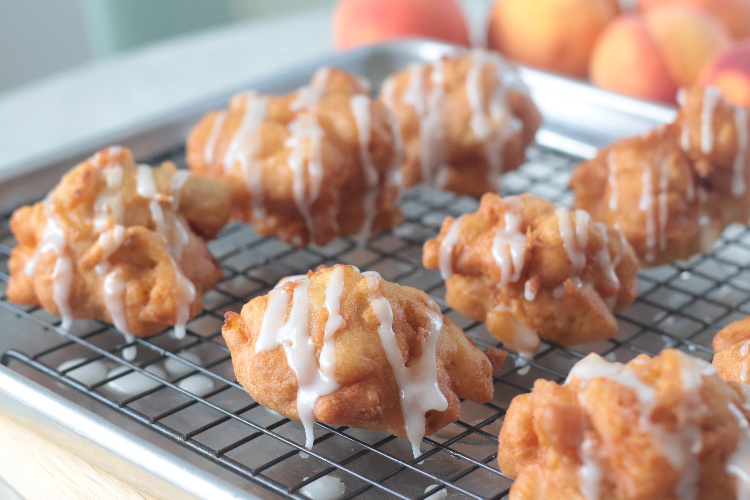 fried peach fritters drizzled in glaze on cooling rack