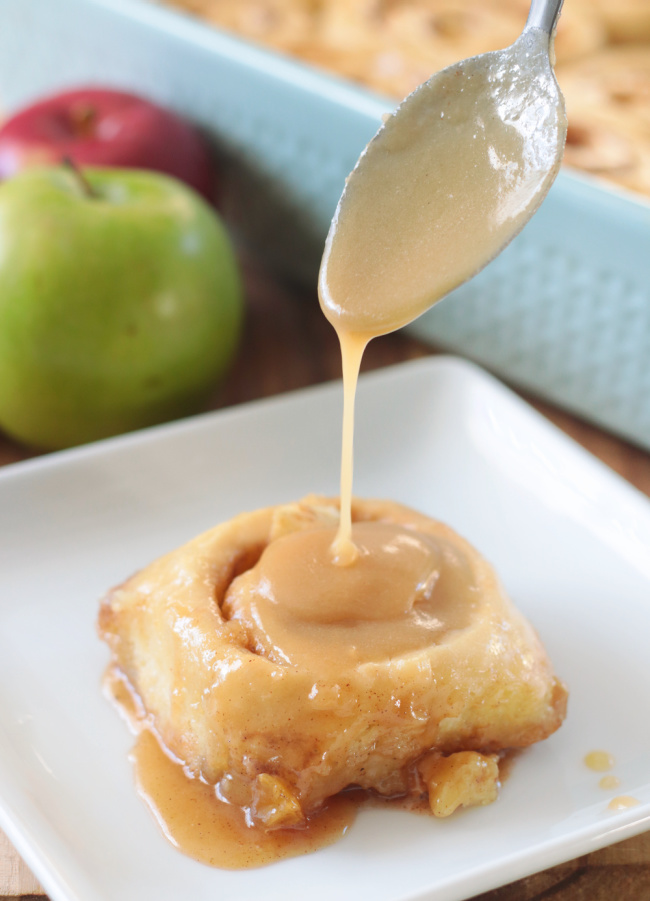spoon drizzling caramel over cinnamon roll