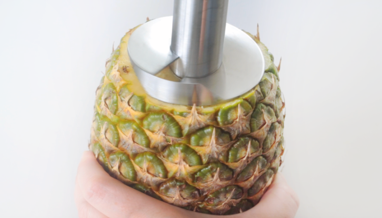 fresh pineapple being cored with kitchen tool